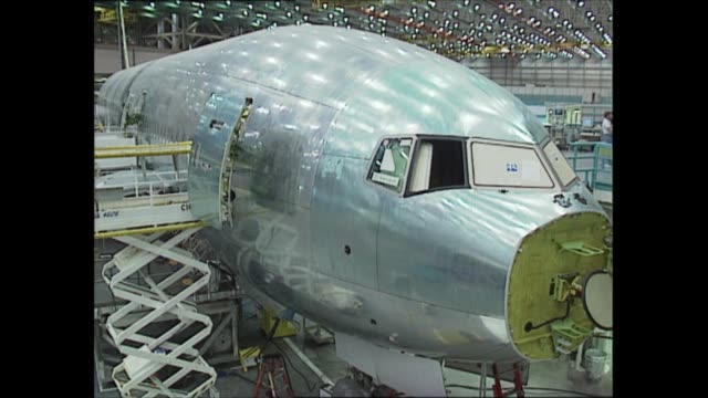 stockvideo's en b-roll-footage met boeing 777 usa seattle int various shots engineers working on plane gv hangar poster for boeing 777 engineers placing boards on floor of plane... - new not politics