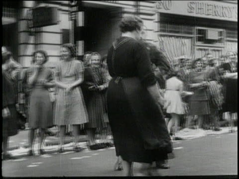 stockvideo's en b-roll-footage met british and american flags wave as hundred of citizens soldiers men and women gather together dancing and cheering celebrating ve day in trafalgar... - geallieerde mogendheden
