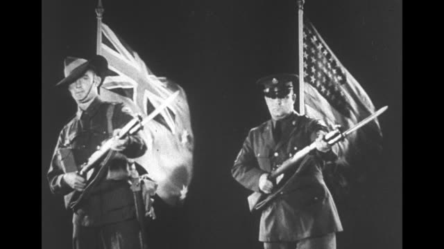 british and american soldiers with guns upraised standing in front of waving union jack american flags / note exact day not known - 多国籍軍点の映像素材/bロール