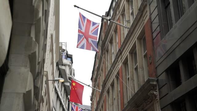 Drapeaux britanniques et chinois agitant dans la City de Londres