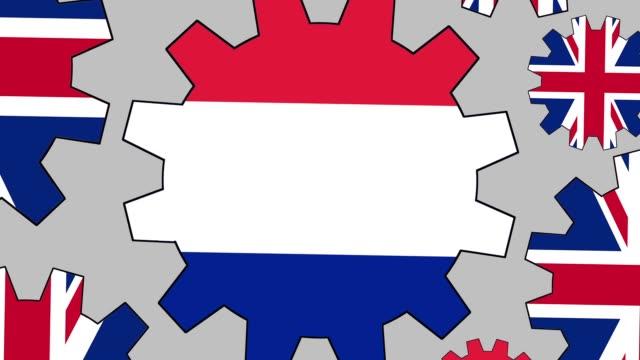 vidéos et rushes de engrenages de drapeau britannique et français tourne à fond de zoom arrière - royaume uni