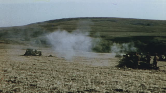British Army 25pounder artillery firing the battery commanding calling fire and black smoke signaling a hit / Tunisia