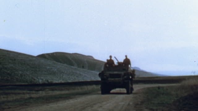British Army armored scout car traveling on a dirt road followed by a US Army halftrack on reconnaissance / Tunisia