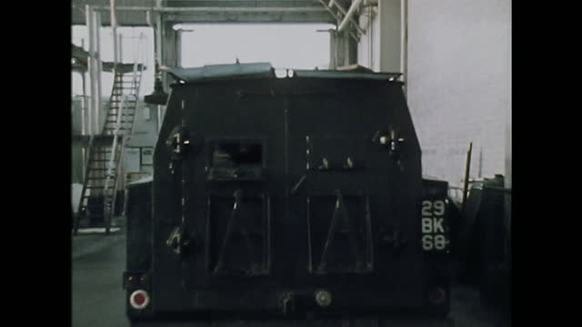 british army armoured vehicle departs barracks to go on patrol in belfast, northern ireland; 1971. - government building stock videos & royalty-free footage