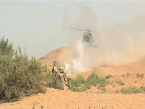 british army helicopter prepares to land as pair of officers seek shelter behind bushes during battle afghanistan 2 december 2009 - 2001年~ アフガニスタン紛争点の映像素材/bロール