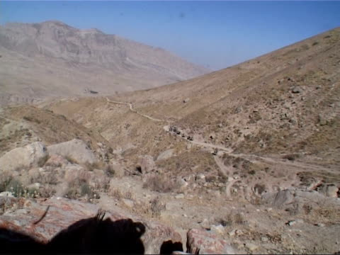 british army patrol on horseback in mountains of the samangan province; patrol wind around side of mountain on rocky path forwards pull out to show... - zigzag stock videos & royalty-free footage