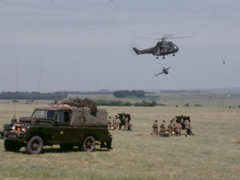 A British army puma helicopter transports a field gun during a NATO training exercise on Salisbury Plain