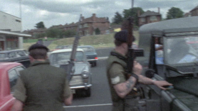 vídeos y material grabado en eventos de stock de 1973 montage british army soldiers checking cars outside a retail center / northern ireland - irlanda del norte
