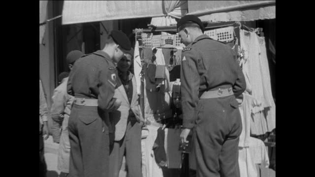 montage british army soldiers on leave strolling through the streets of tripoli, browsing at a street market, talking with locals, and photographing them / libya - british military stock-videos und b-roll-filmmaterial