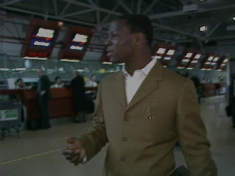 british boxer chris eubank walks through the heathrow departures area. typically smartly dressed he jokes with cameraman before walking towards... - chris eubank sr stock videos & royalty-free footage