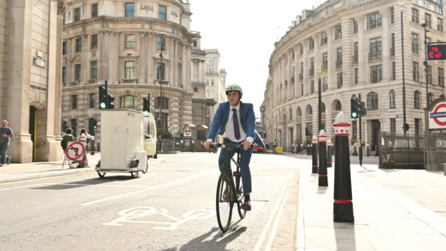 british businessman enjoying freedom of cycling to work - moving past stock videos & royalty-free footage
