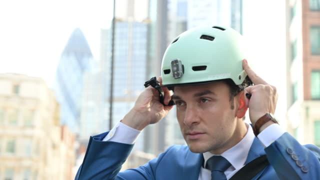 british businessman putting on bike helmet for commute - white caucasian stock videos & royalty-free footage