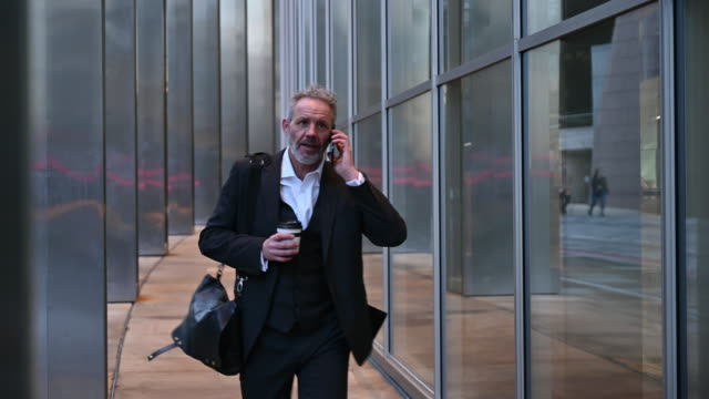 british businessman using smart phone and walking briskly - full suit stock videos & royalty-free footage