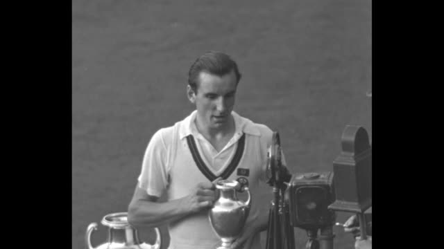 vidéos et rushes de british citizen fred perry gives a statement after wining the us open against wilmer allison for the second straight year / perry holding trophy - trophée