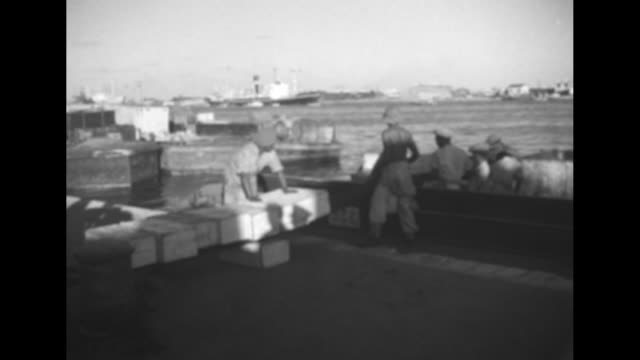 british colonial soldiers unloading cargo from barge onto dock on suez canal / three shots of soldiers unloading cargo from truck onto dock using... - suez canal stock videos & royalty-free footage
