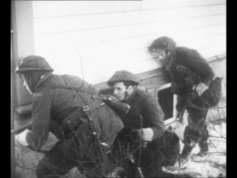 british commandos move through snow pass buildings during raid on vagsoy norway during world war ii / soldiers' legs as they crouch move forward... - plunger stock videos and b-roll footage