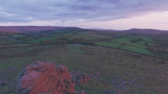 vidéos et rushes de british countryside landscape in dartmoor national park at sunrise, devon, england, uk. aerial drone view - violet