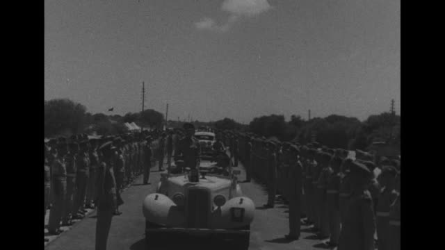 british flag and king's standard / american troops at attention during visit of king george vi to wwii north african front / field marshal bernard... - vangen bildbanksvideor och videomaterial från bakom kulisserna