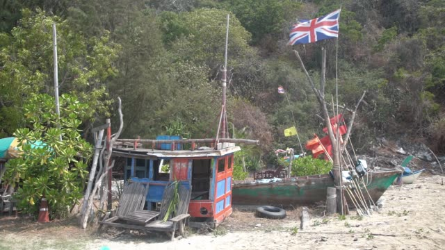 british flag fluttering in the breeze on ban krut beach in an almost pirate like scene complete with vegetation in background - gold coloured stock videos & royalty-free footage