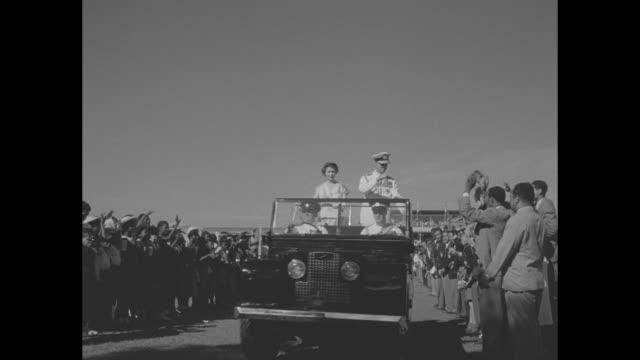 vídeos y material grabado en eventos de stock de british flag hanging in front of camera, spectators in background / elizabeth ii and prince philip riding in open jeep and waving to spectators /... - visita de estado
