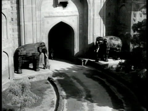 British flag on fort guard patrolling on watch tower HA WS English soldiers marching through underpass gates w/ two large elephant statues MS...