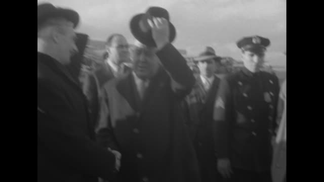 British Foreign Secretary Anthony Eden his wife Clarissa policemen and crowd of officials walking towards camera / Clarissa shaking hands with Sir...