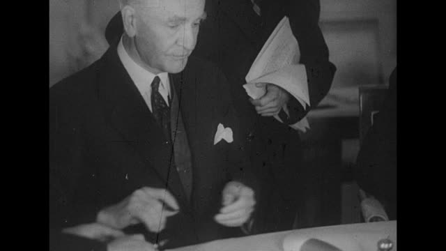 british foreign secretary anthony eden signs declaration soviet minister vyacheslav molotov looks on and blots ink on previous signature / united... - cordell hull stock videos and b-roll footage