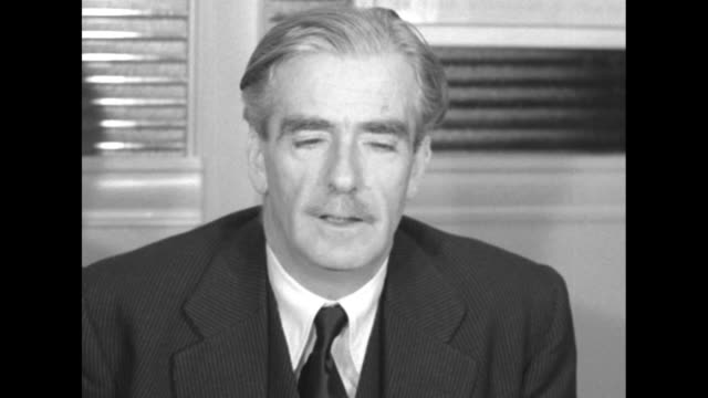 British Foreign Secretary Anthony Eden sits down in chair at desk gets ready to speak to press / two shots of Eden speaking to camera about his just...
