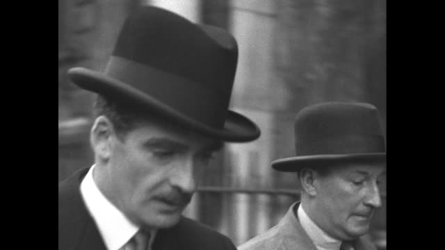 VS British Foreign Secretary Sir Anthony Eden leaves 10 Downing Street carrying an umbrella he walks past camera / Note exact month/day not known