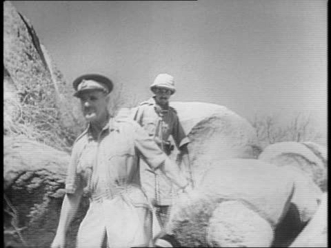 vidéos et rushes de british general archibald wavell climbs through boulders / wavell points out possible artillery targets with a cane / soldiers unload mortar shells... - armée de terre
