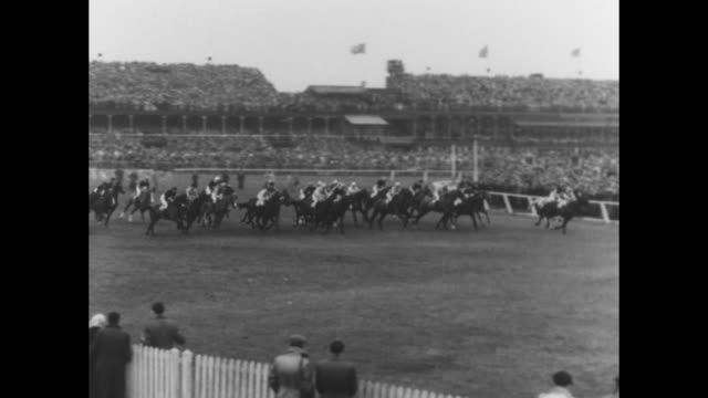 british grand national at aintree racecourse / a race in progress / horses with jockeys take the second jump / ws royal party includes queen... - hurdling horse racing stock videos and b-roll footage