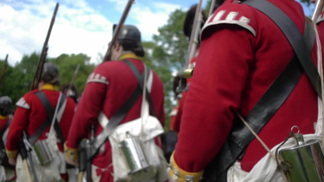 british grenadier soldiers march with muskets on their shoulders during a revolutionary war reenactment. - army soldier stock-videos und b-roll-filmmaterial
