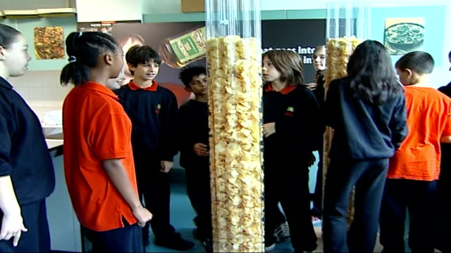 british heart foundation food4thought campaign: children warned about fat in crisps; school children looking at see-through pillars filled high with... - snack stock videos & royalty-free footage