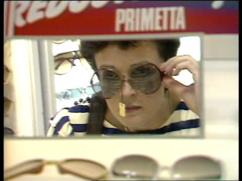 stockvideo's en b-roll-footage met british heatwave the beatles 'good day sunshine' ** england london selfridges cms girl trying on sunglasses as looks in mirror cms man trying on... - wandsworth