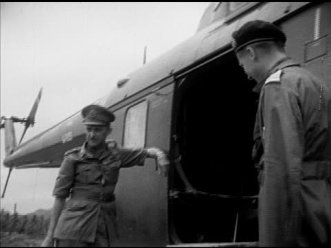 British High Commissioner General Sir Gerald Templer leaving walking toward Sikorsky S55 Royal Navy helicopter waiting for Lady Edith Templer to...