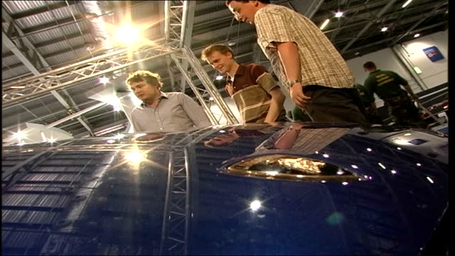 british international motor show visitors looking at cars posing for photographs chatting among exhibits / toyota cars - トヨタ自動車点の映像素材/bロール