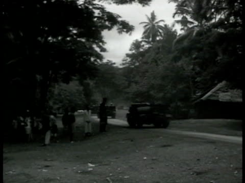 british light armored tanks on road passing south pacific island natives. english open-top light armored tanks driving through forest. ext european... - pazifikinsulaner stock-videos und b-roll-filmmaterial