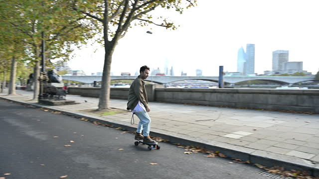 british male skateboarder commuting along thames embankment - sustainable energy stock videos & royalty-free footage