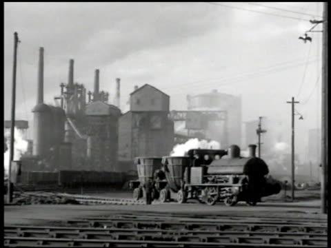 british man & train, factory bg. ext workers entering factory gates. int vs men working w/ machine drill, machinery. woman working machine lathe.... - home economics点の映像素材/bロール