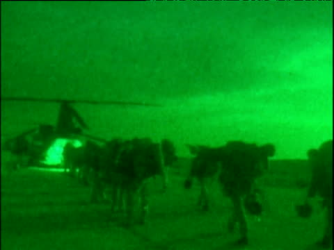 British Marines approaching and boarding helicopter at Bagram airbase War in Afghanistan 2001