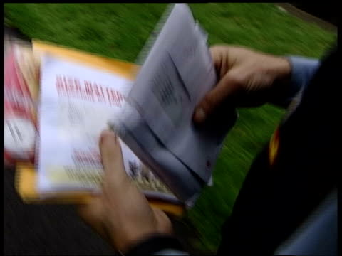 british national party: election material: postmen refuse to deliver:; ???: tcms letters being carried by postman track int cms letter pushed thru... - letterbox stock-videos und b-roll-filmmaterial