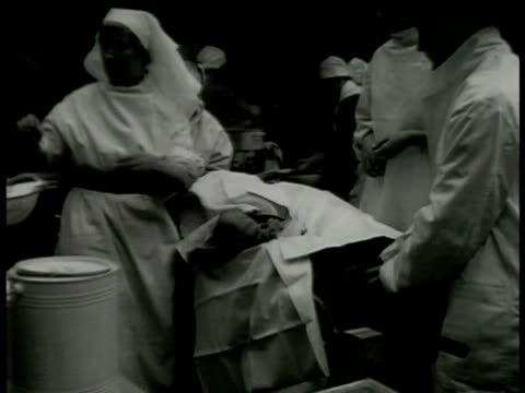 british nurses & doctors operating on patient tearing patient's clothes. doctors & nurses operating on injured patient's leg bandages leg stretcher.... - red cross stock videos & royalty-free footage