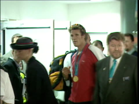 British Olympic team greeted by fans at airport ENGLAND Heathrow Airport Audley Harrison towards as pushing luggage trolley speaks to press holds up...