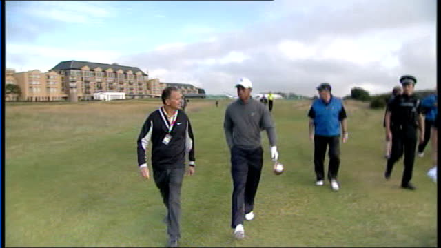 vidéos et rushes de tiger wood speaks to press scotland st andrews ext tiger woods striking golf ball with club silhouetted against sky woods walking across course woods... - écosse