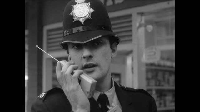 montage a british police officer on a radio calling the police station where an officer and a typist are working / chester, england, united kingdom - cheshire england stock videos & royalty-free footage
