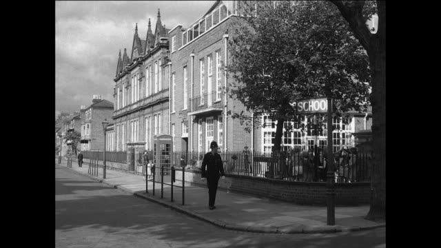 montage a british policeman patrolling his beat at a marketplace, an empty street of warehouses, a school and a city park before calling into police headquarters / united kingdom - report document stock videos & royalty-free footage