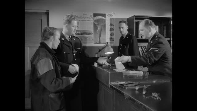 stockvideo's en b-roll-footage met montage british policemen taking a criminal into custody at the station and reading him his rights / united kingdom 1950's - politiestation