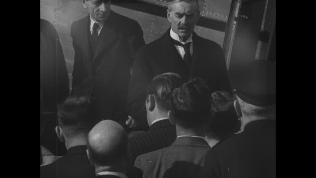 british prime minister neville chamberlain is seen behind a crowd of reporters and his british airlines plane at heston aerodrome / sot a peaceful... - 1938 stock-videos und b-roll-filmmaterial