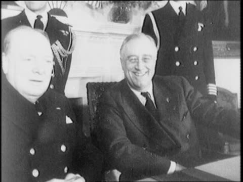 british prime minister winston churchill and american president franklin delano roosevelt sit at a desk at the white house laughing and smiling - anno 1941 video stock e b–roll