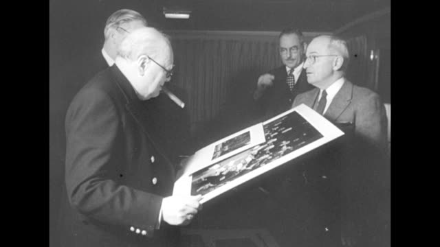ms british prime minister winston churchill cigar in mouth holds very large and small photographs in hands and looks at them us president harry s... - minister president stock videos and b-roll footage